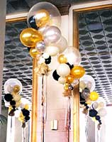 Giant floating bubble decorations using clear, gold, silver and black balloons for a formal event