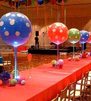 20 inch balloons in sorbet colors sit on 14 inch tall glass vases filled with sand matching the color of the balloons.  Lighting in the bases gives a radiating glowing color.