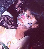 Girl at Halloween party having her face painted as a skeleton