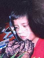 Girl at Halloween party having a spiter web painted on her