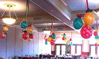 Red and green Holiday Ornament balloons suspended from the ceiling throughout a venue