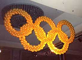 Giant lighted Olympic ring sculpture suspended from the venue ceiling for a corporate competition event
